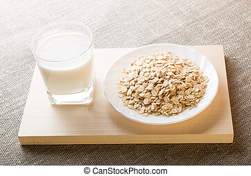 Glass of milk and a plate of cereal closeup