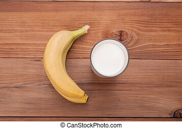 Glass of milk and bananas on a wooden background.
