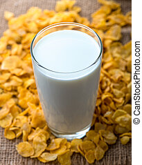 glass of milk and cereals on the wooden table