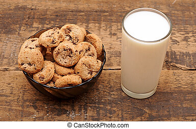 Glass of milk and chocolate chip cookies on wooden table