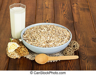 Glass of milk and oatmeal on wooden background