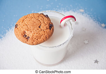 Glass of milk, cookies and candy cane on the blue background