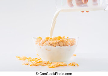 Glass of milk is being poured into cornflakes bowl.