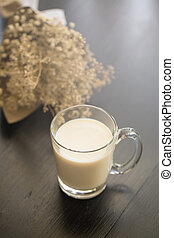 Glass of milk on black wooden background