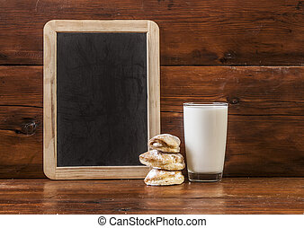 glass of milk on wooden table with cookies