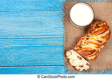 glass of milk with a loaf of bread on a blue wooden background with copy space for your text. Top view