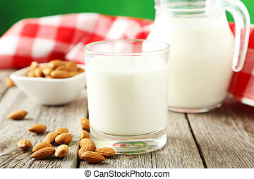 Glass of milk with almonds on grey wooden background