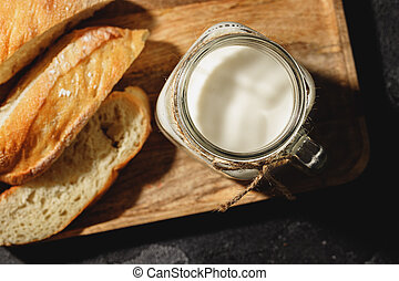 Glass of milk with bread slices on black surface