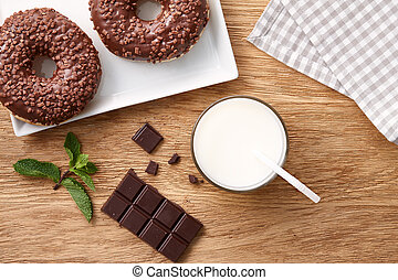 Glass of milk with chocolate donuts on wooden table