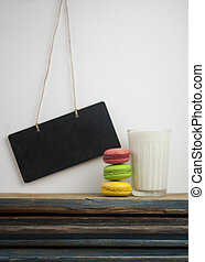 Glass of milk with colorful macaroons on wood table over white wall and blank blackboard