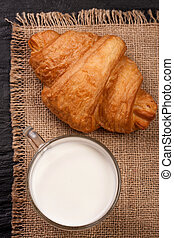 glass of milk with croissant on sackcloth . Top view