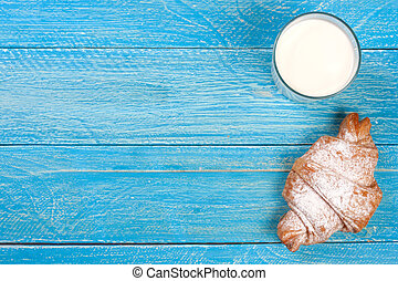 glass of milk with croissants on a blue wooden background with copy space for your text. Top view