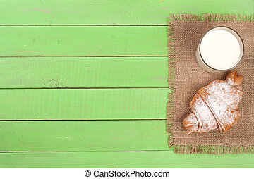 glass of milk with croissants on a green wooden background with copy space for your text. Top view