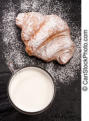 glass of milk with croissants on black stone background . Top view