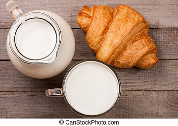 glass of milk with croissants on old wooden background. Top view