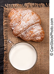 glass of milk with croissants on sackcloth . Top view