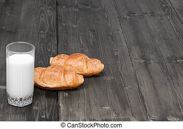 glass of milk with pair of croissants on a old grey rustic wooden background with copy space for your text. Top view
