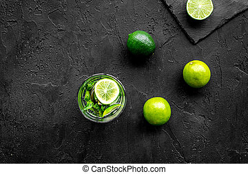 Glass of mojito, lime, mint on black stone background top view copyspace