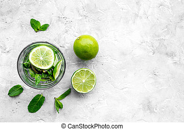 Glass of mojito, lime, mint on grey stone background top view copyspace