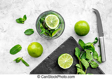 Glass of mojito, lime, mint on grey stone background top view
