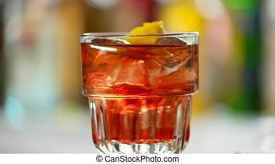 Glass of negroni rotating. Red drink with lemon peel. Sweet...