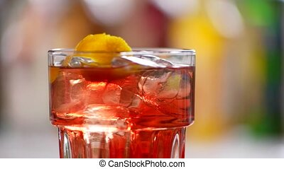 Glass of negroni turning around. Ice cubes inside red...