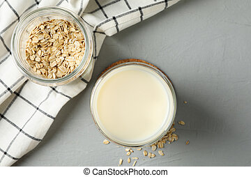 Glass of oat milk, oatmeal seeds, napkin on grey background, space for text. Closeup