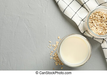 Glass of oat milk, oatmeal seeds, napkin on grey background, space for text. Top view