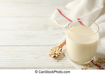 Glass of oat milk, spoon with oatmeal seeds and napkin on white, wooden background, space for text. Closeup