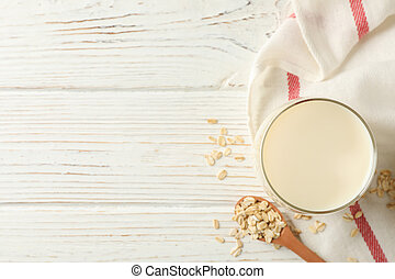 Glass of oat milk, spoon with oatmeal seeds and napkin on white, wooden background, top view. Space for text