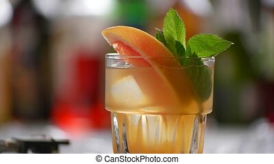 Glass of orange beverage rotates.