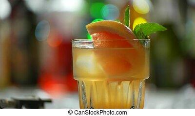 Glass of orange cocktail rotates.