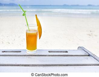 Glass of orange colour juice on the beach