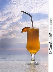 glass of orange juice on sky background