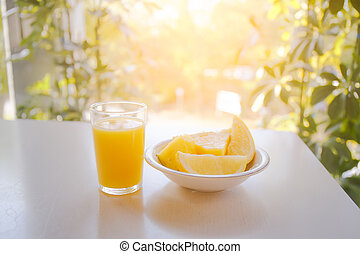 Glass of orange juice on the table with sunlight in the background.