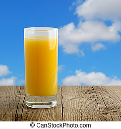 Glass of orange juice on wooden table on blue sky background