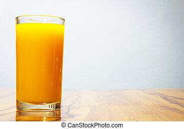 glass of orange juice on wooden table