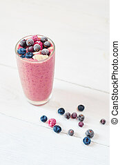 Glass of pink fruit smoothies milkshake or cocktail on white background, breakfast vegan and raw food, with a place for your text