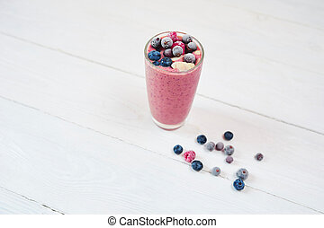 Glass of pink fruit smoothies milkshake or cocktail on white background, breakfast vegan and raw food, with a place for your text, concept of raw food