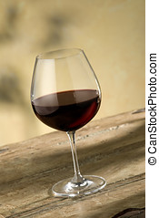 glass of pinot noir wine on rustic wooden table, warm...