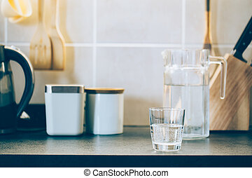 Glass of pure water on kitchen table.