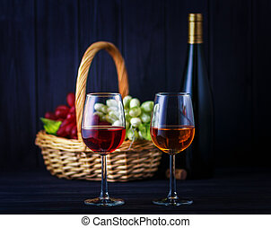 Glass of red and white wine with a defocused bottle and fruits on back