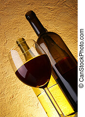 Glass of red wine and bottles
