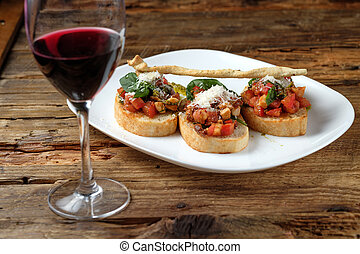 Glass of red wine and bruschetta with fresh tomatoes, parmesan and basil