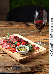 Glass of red wine and cutting board with assorted smoked meat