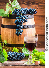 Glass of red wine and grapes in the cellar