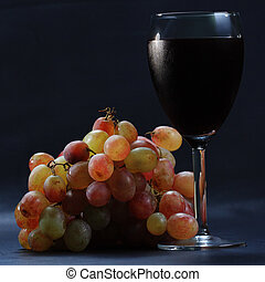 Glass of red wine and grapes sideview