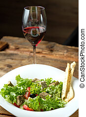 Glass of red wine and vegetarian salad with cheese and vegetables