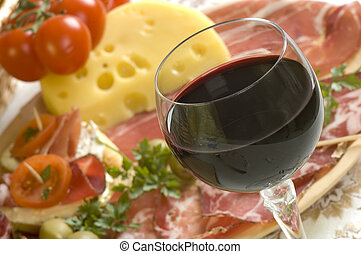wine - glass of red wine close up with food in background