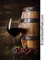 Glass of red wine, grape and barrel
